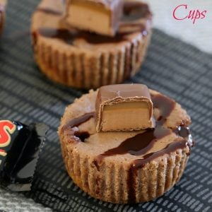Two individual Mars Bar cheesecakes, drizzled with chocolate sauce and a cut piece of Mars Bar on top,