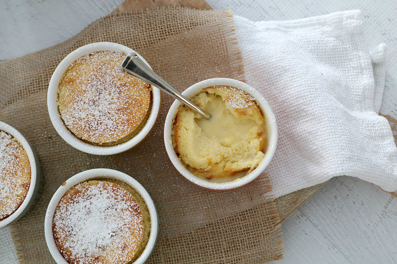 Three individual ramekins filled with lemon pudding dusted with icing sugar, and a spoon in one half eaten dish