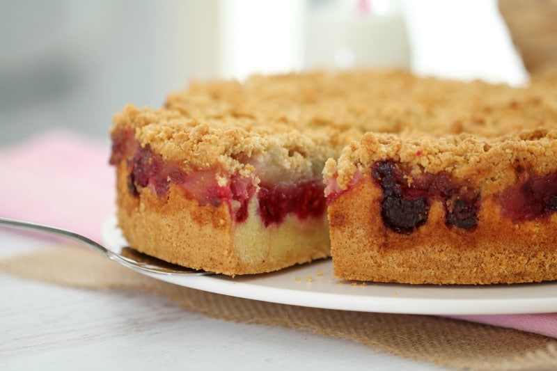 A side view of an cake showing layers of apple and raspberry and a crumble topping served on a plate with one slice removed