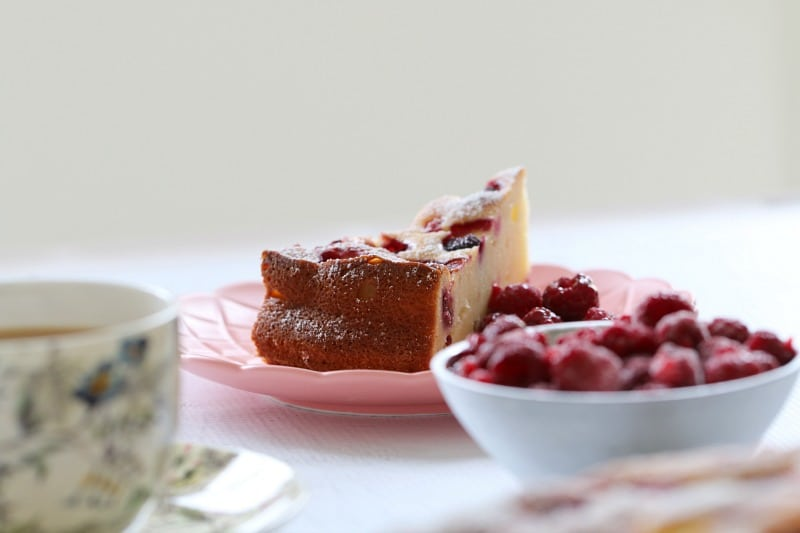 A serve of a cake made with raspberries and ricotta served on a pink plate with a bowl of fresh raspberries beside