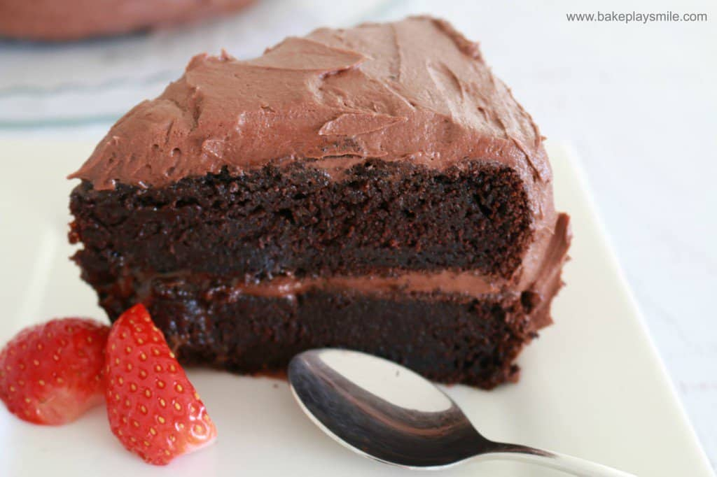 A wedge of chocolate cake layered and covered with chocolate frosting, with a spoon and fresh strawberry beside