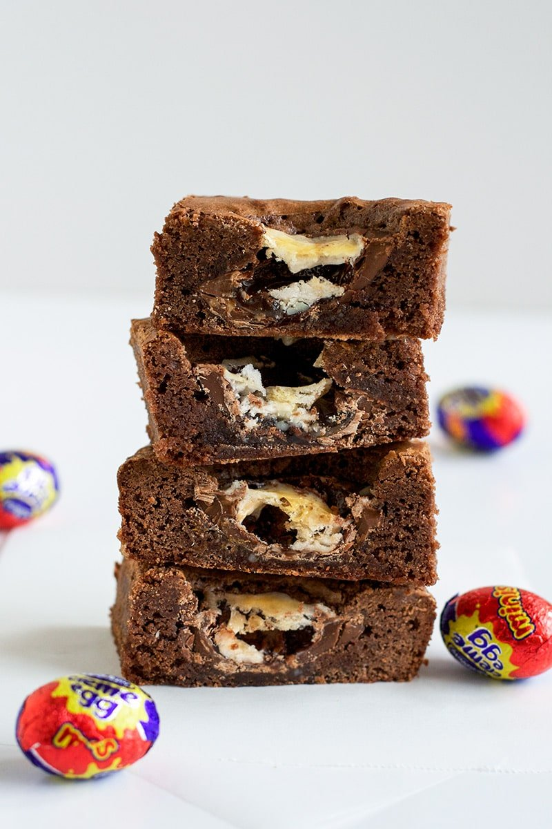 A stack of cut pieces of brownie slice showing a filling of Cadbury Creme Egg melted through the centre