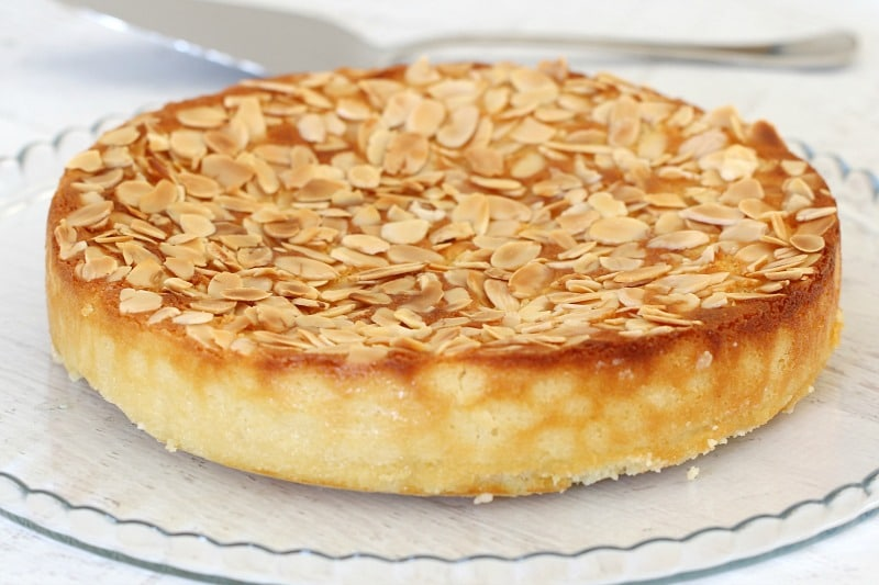A round lemon cake topped with toasted flaked almonds, served on a glass plate