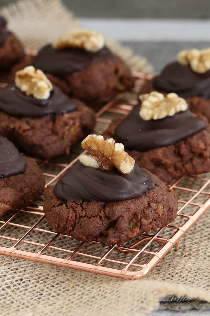 Chocolate cookies topped with melted dark chocolate and a walnut on a copper wire rack.