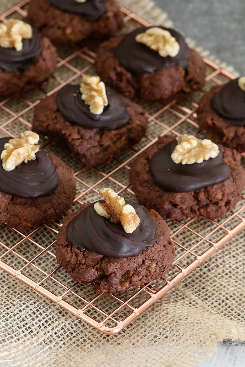 A tray of chocolate cookies with chocolate icing and walnuts on top.