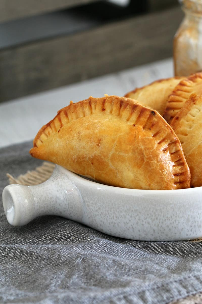 Several empanadas piled into a white serving bowl