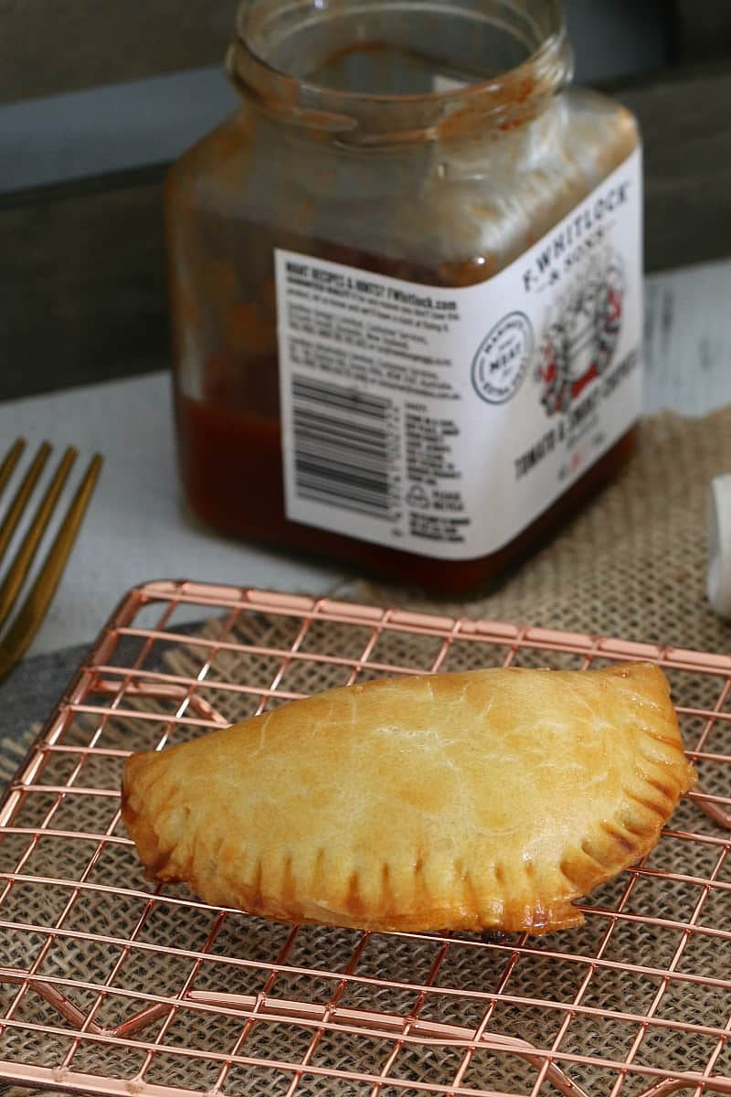 An empanada on a copper wire tray in front of a jar of relish