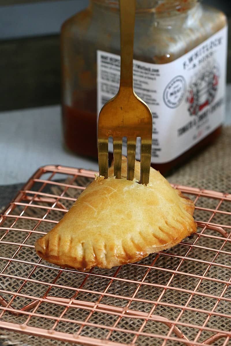 A fork standing up in an empanada on a copper wire tray, with a jar of relish in the background