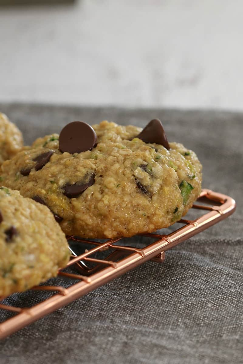 A close up of a cookie made with oats, chocolate chips and zucchini on a copper wire tray