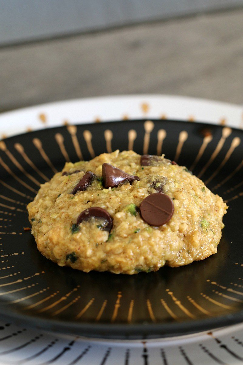 A cookie filled with chocolate chips and zucchini on a black and gold plate