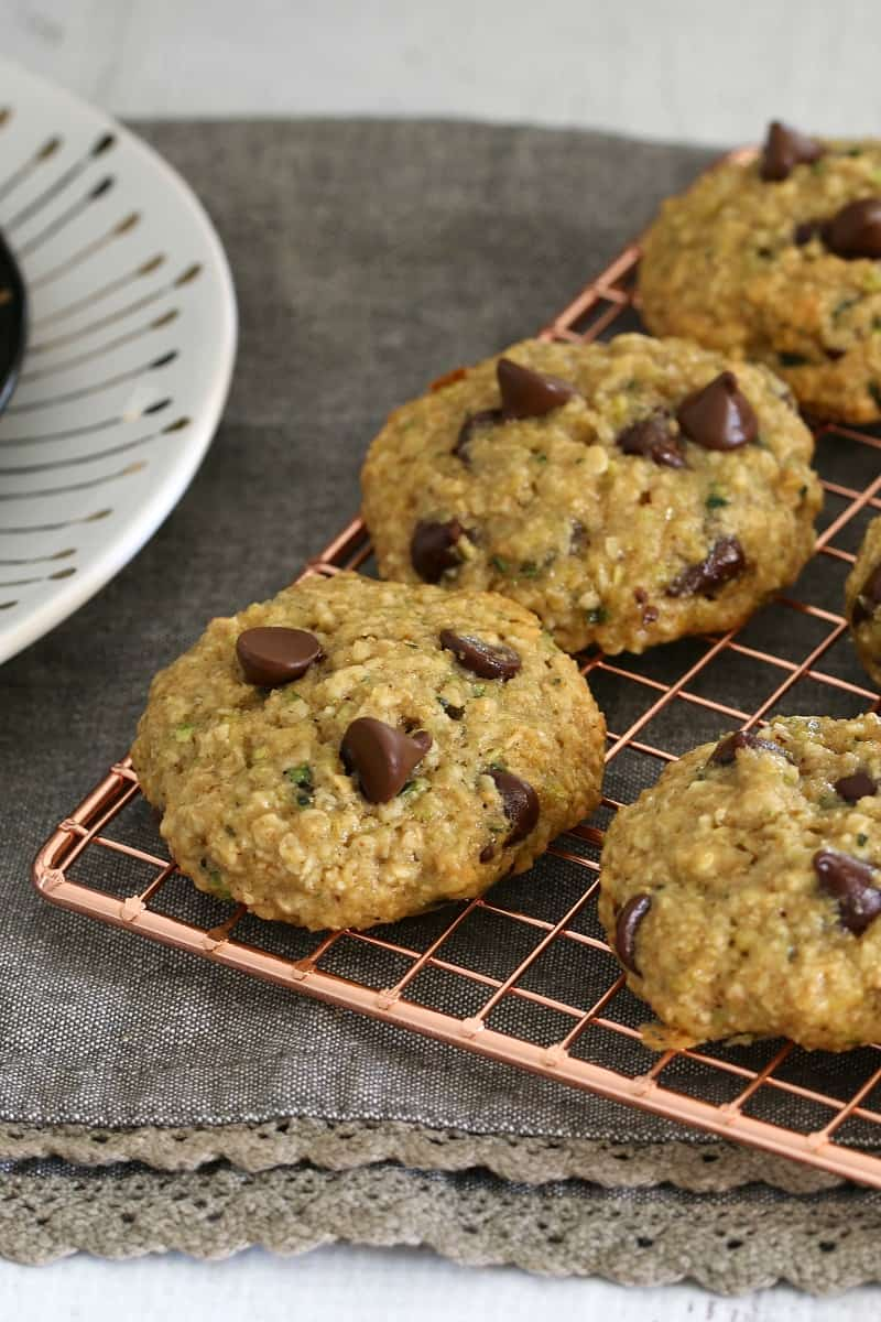 Cookies filled with oats, zucchini and chocolate chips on a copper wire tray