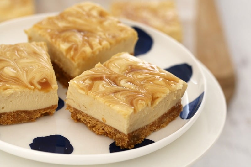 Three squares of a salted caramel cheesecake slice with caramel swirled through on top on a white plate with blue dots