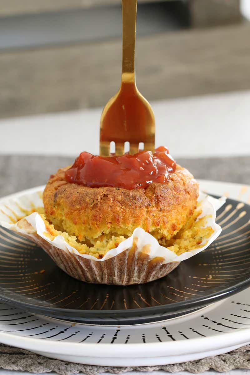 A fork standing up in a savoury muffin topped with relish and served on a black plate