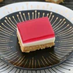 A piece of pink jelly slice on a black plate