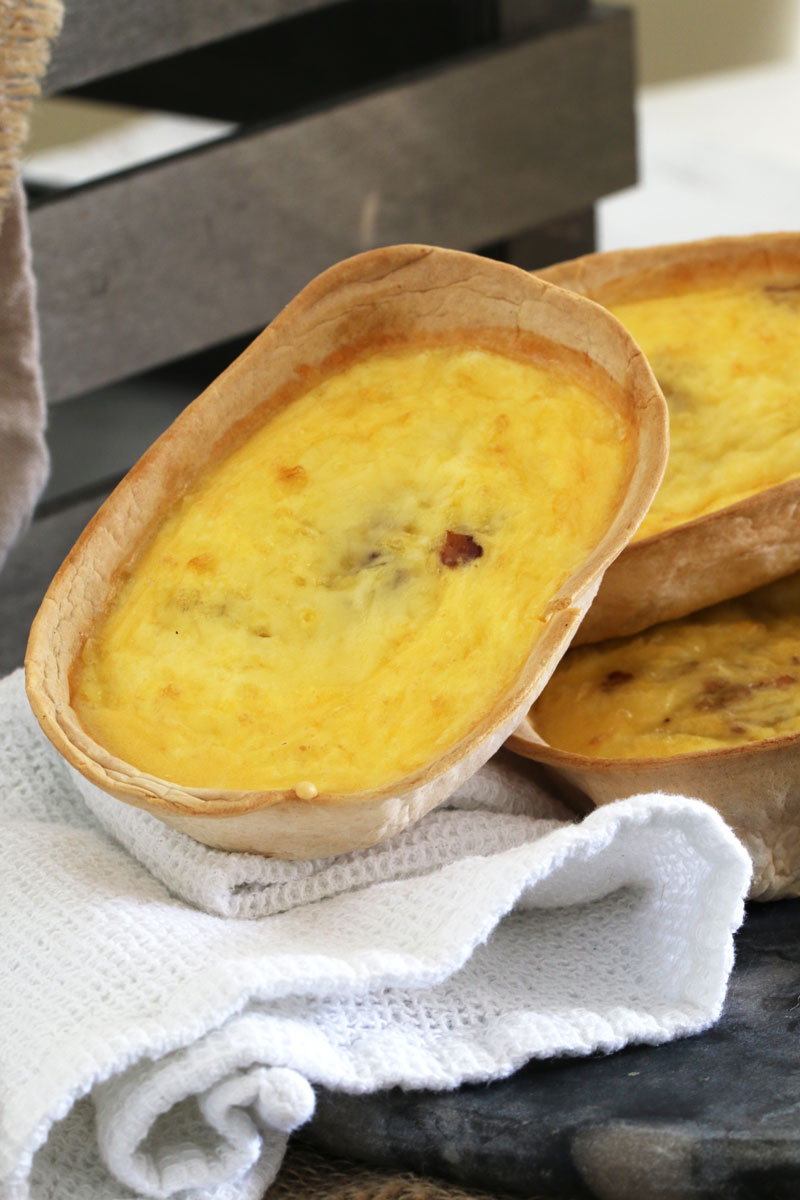 Close up of tortilla shells with a quiche filling and stacked on a tea towel