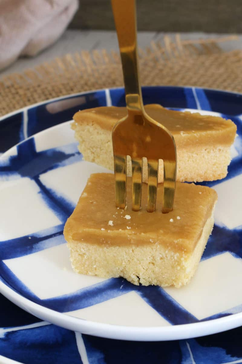 A fork standing upright in a piece of ginger crunch slice served on a blue and white plate
