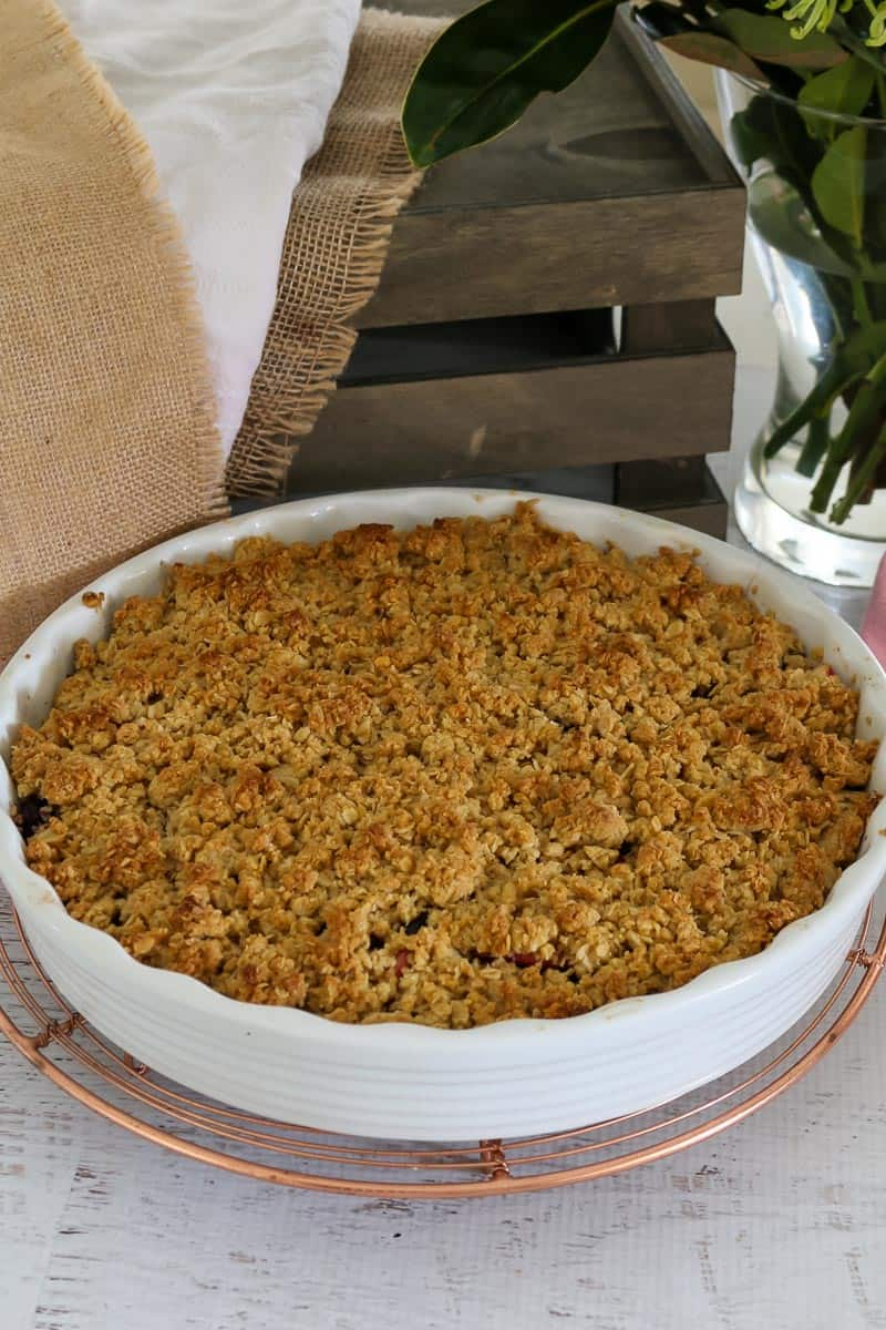 A round baking dish with fruit and crumble.