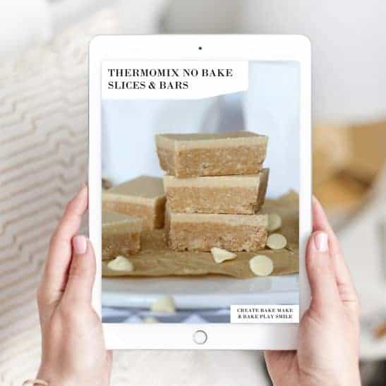 Two hands holding up a Thermomix No Bake Slices and Bars recipe book