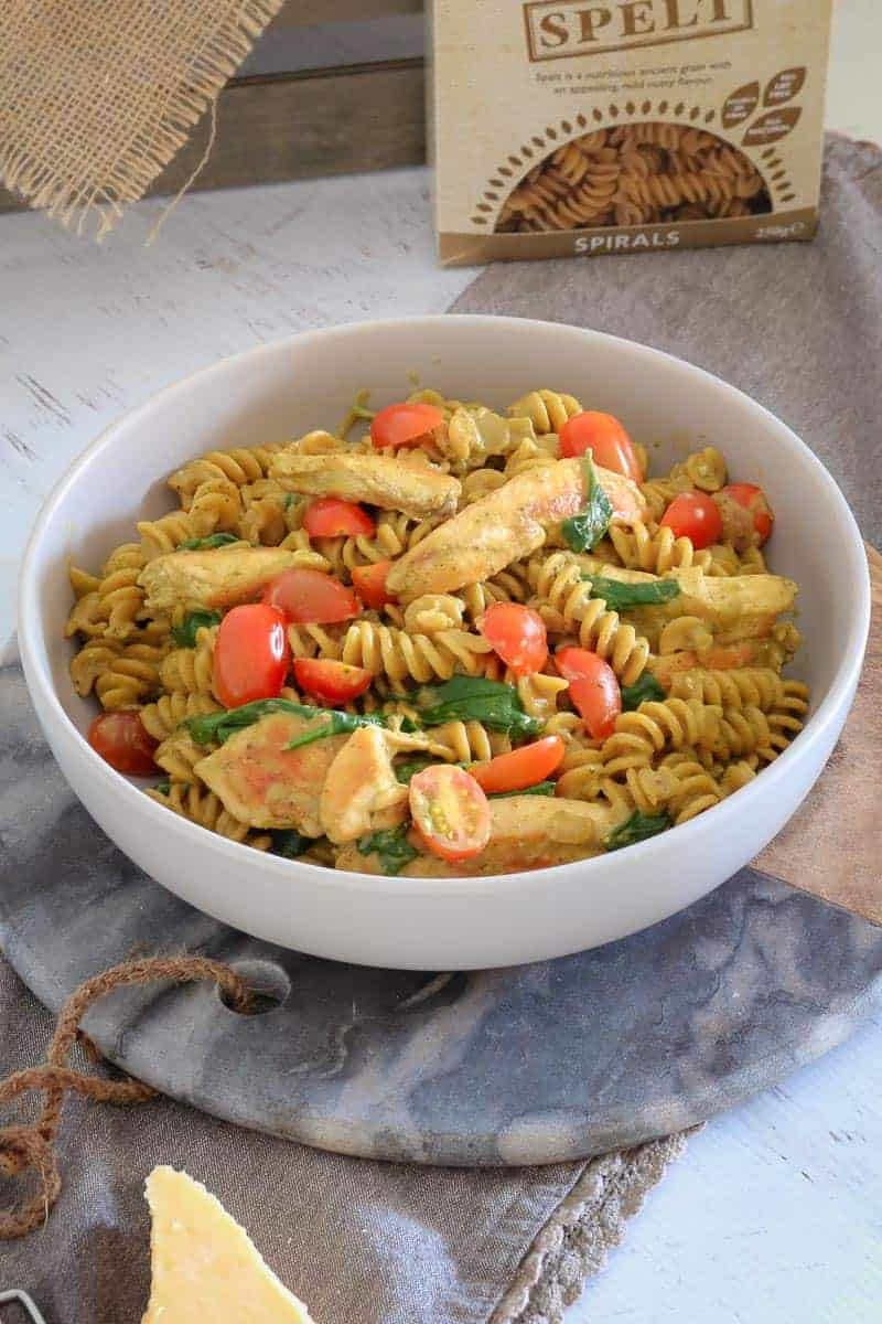 A white bowl of pasta, chicken, cherry tomatoes and spinach, sitting on a marble and wooden board
