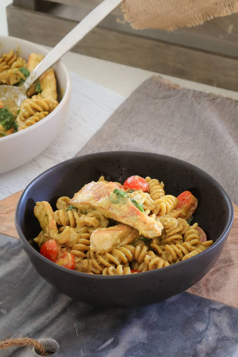 A bowl of pasta, chicken, cherry tomatoes and spinach leaves sitting on a grey tea towel