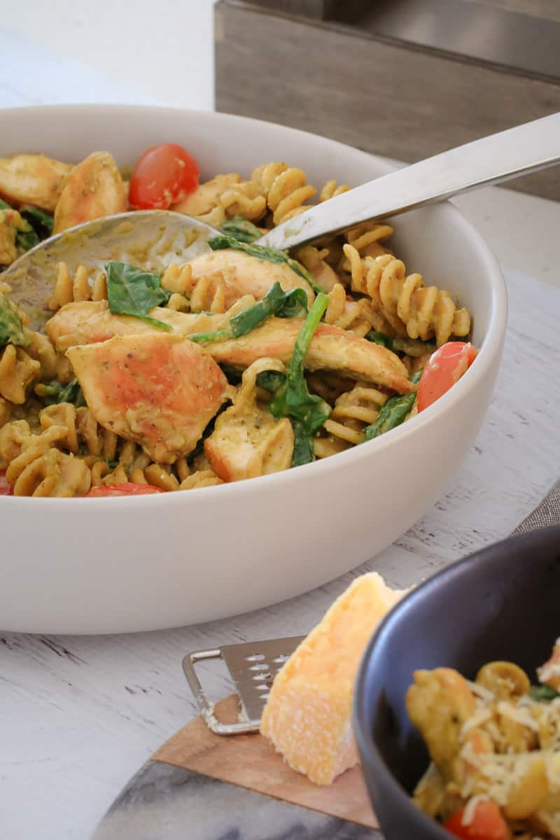 A bowl and spoon of pasta, cherry tomatoes and spinach leaves, on a bench