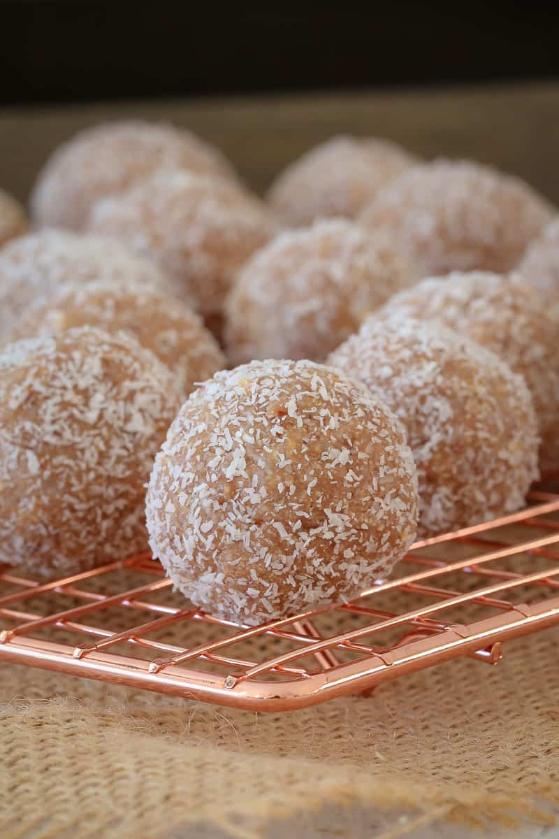 A close up of Milo balls rolled in coconut, sitting on a copper wire tray
