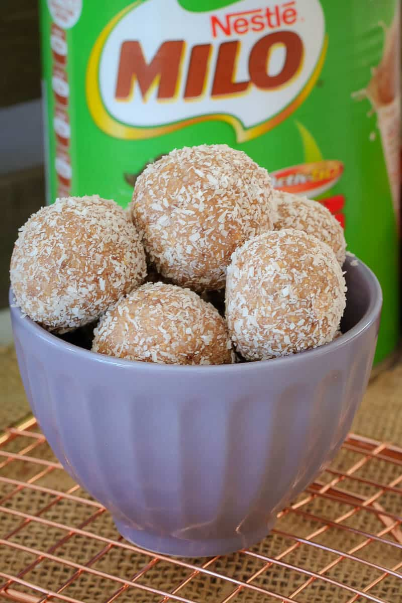 A small blue bowl of Milo balls rolled in coconut, in front of a tin of MIlo