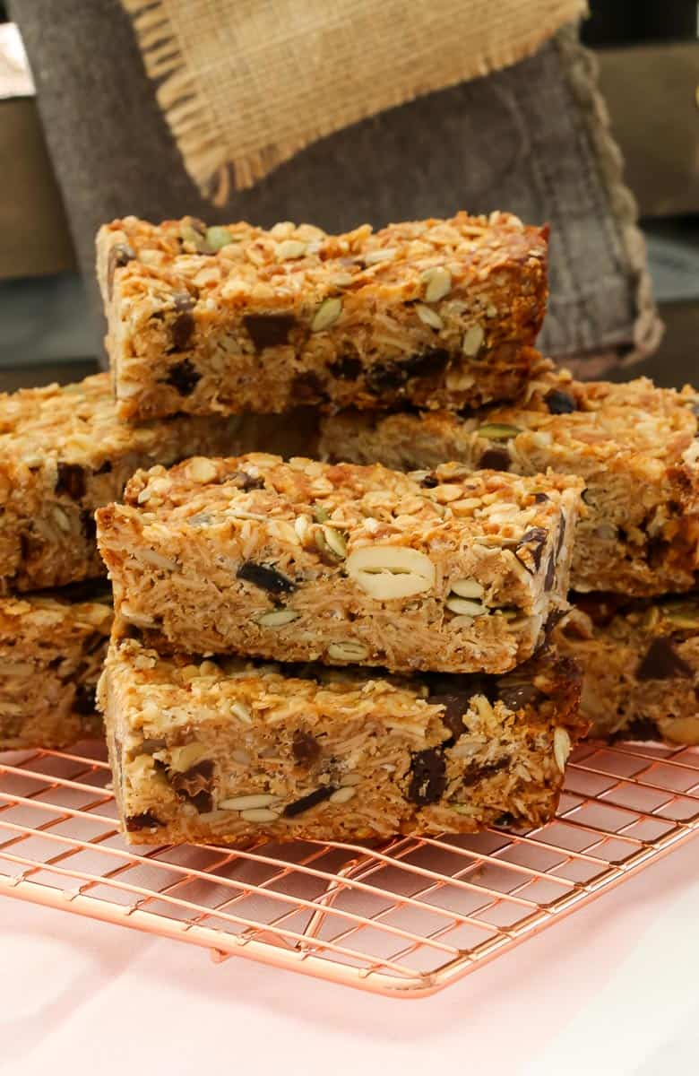 A stack of homemade muesli bars sitting on a copper wire tray
