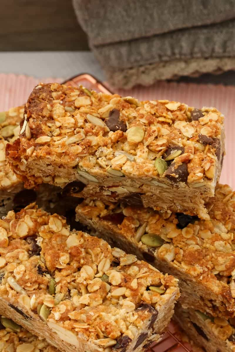 Looking down on a pile of homemade muesli bars, filled with rolled oats, nuts, seeds and dried fruit