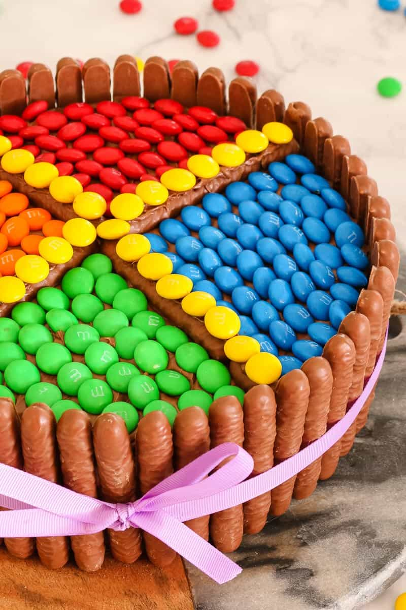 This M&Ms chocolate cake is the perfect birthday cake! It's so simple to make and looks amazing. Decorated with chocolate biscuits, frosting & M&Ms... this is sure to be a hit!