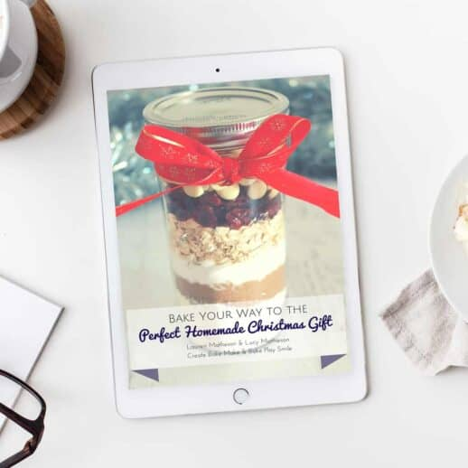 A recipe book 'Christmas Homemade Gifts' with a photo of a jar filled with cookie ingredients and tied with a red ribbon on the cover