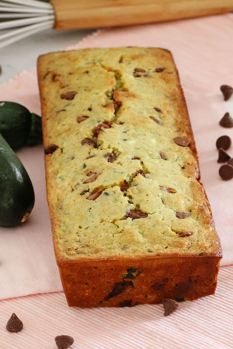 A baked loaf on a bench with zucchini\'s and chocolate chips nearby