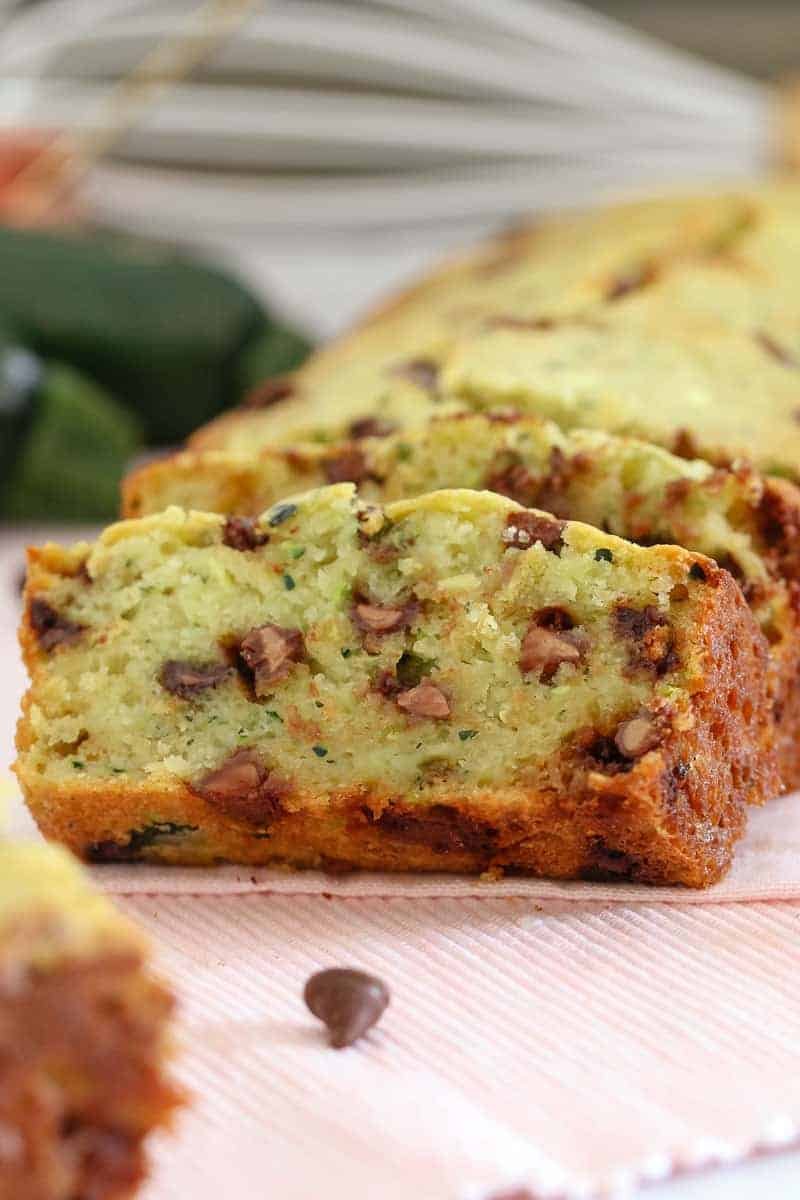A close up of slices of a loaf, made with zucchini and chocolate chips, showing the texture inside