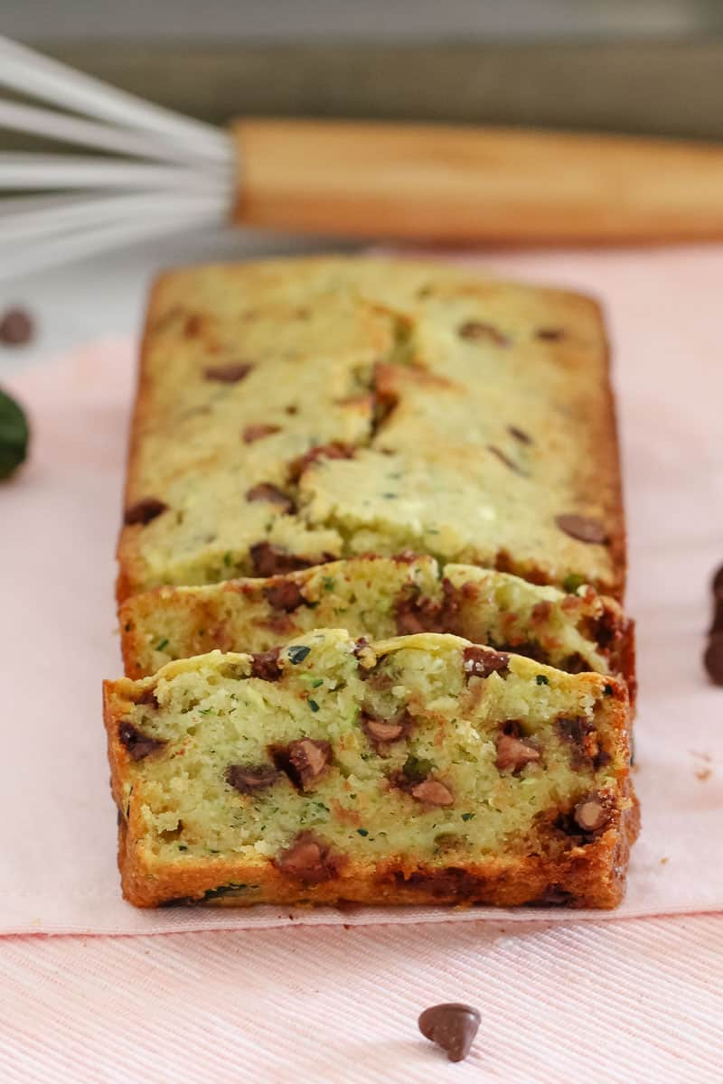 A baked loaf made with zucchini and chocolate chips with the first two slices cut showing texture