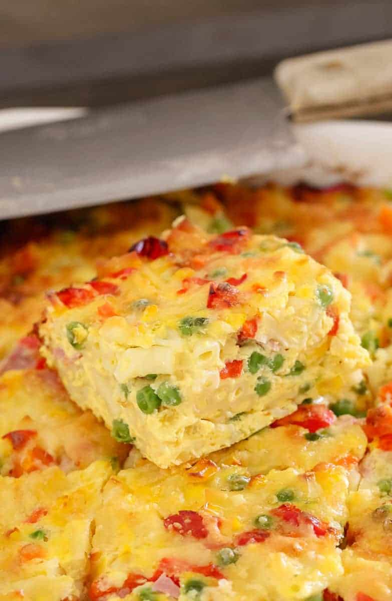 A close up of a baked frittata with a cut piece on top showing a filling of peas, corn and capsicum