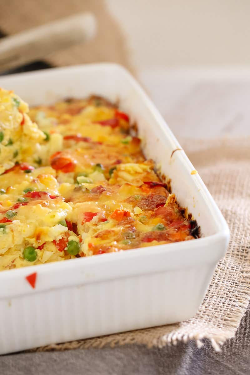 A close up of a white baking dish filled with a frittata made with eggs, macaroni and vegetables