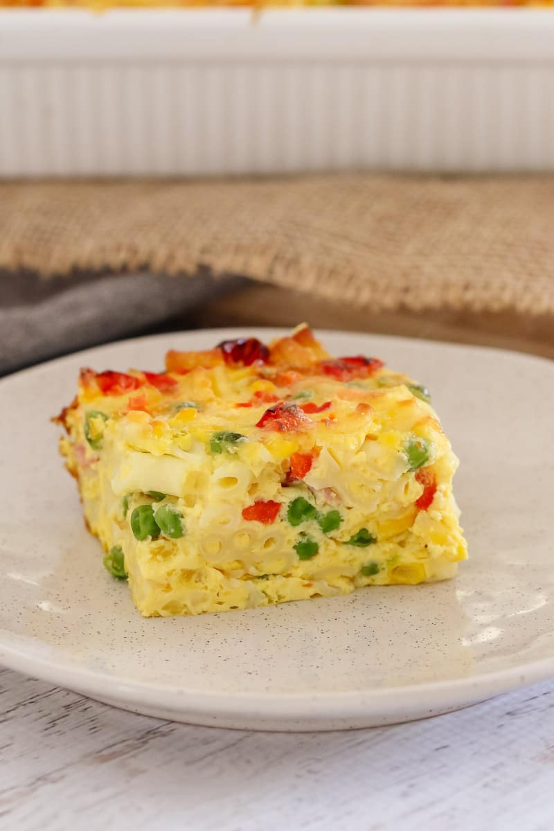 A serve of frittata on a white plate, showing a filling of egg, macaroni, peas, capsicum, corn and ham