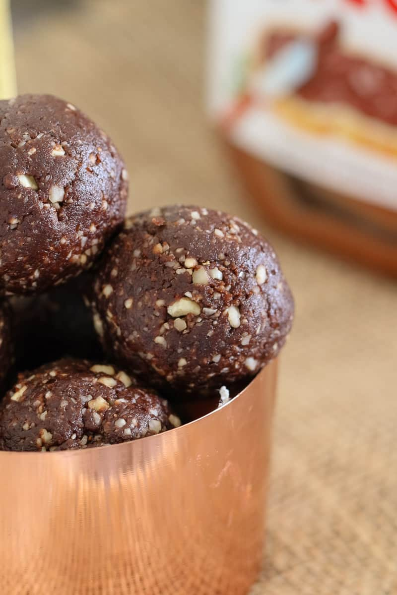A close up of chocolate and hazelnut flavoured Nutella Bliss Balls in a copper measuring cup