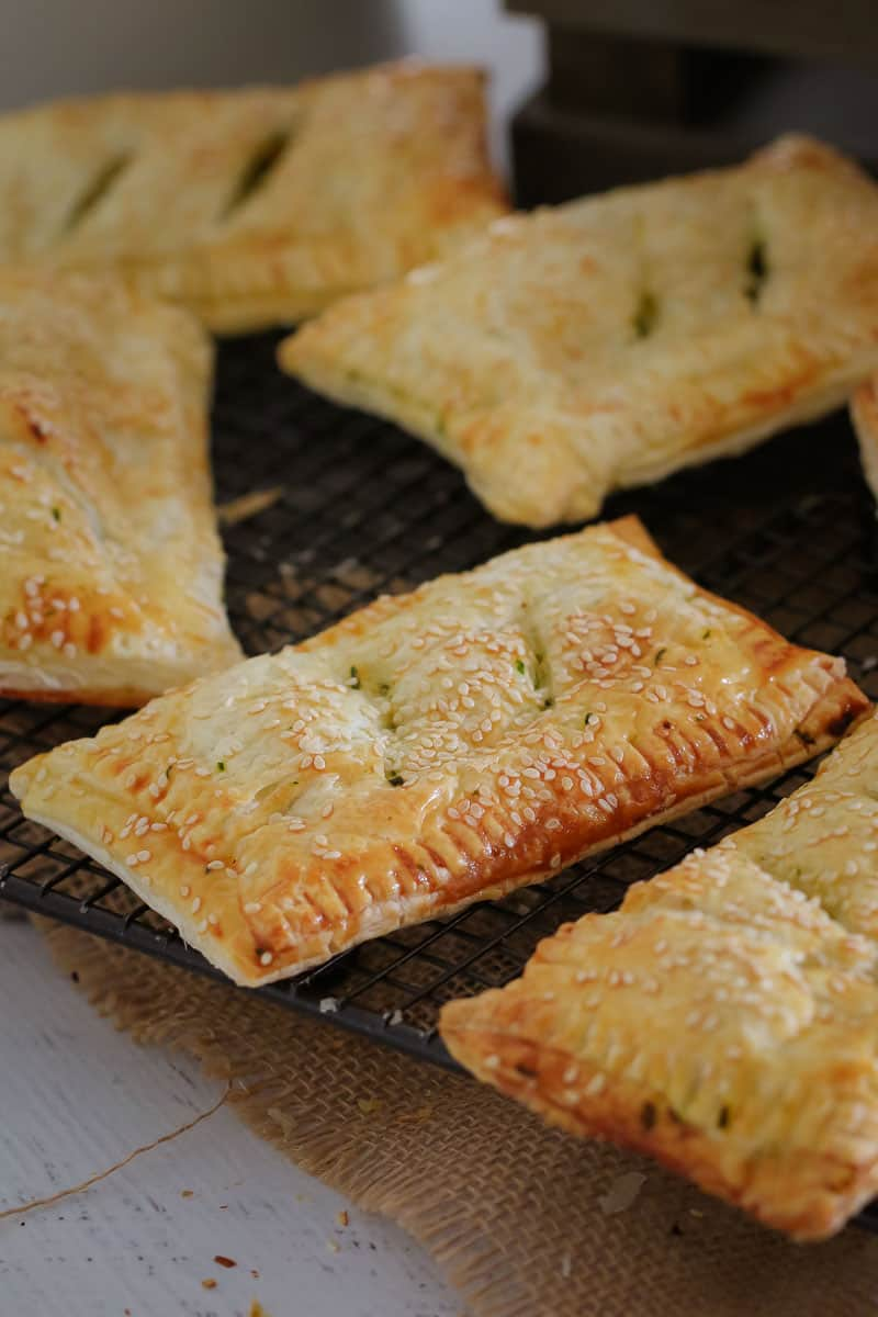 Golden puff pastry rolls sprinkled with sesame seeds on a wire cooling rack
