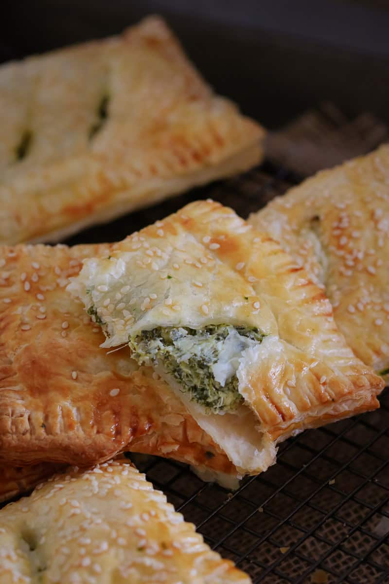 A close up of golden puff pastry rolls on a wire cooling rack with one split to reveal filling of spinach and ricotta