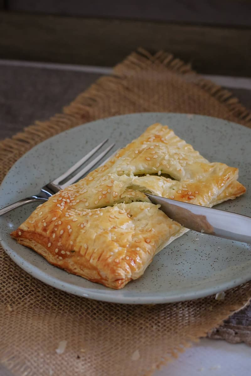 A golden puff pastry roll on a grey plate being cut with as knife