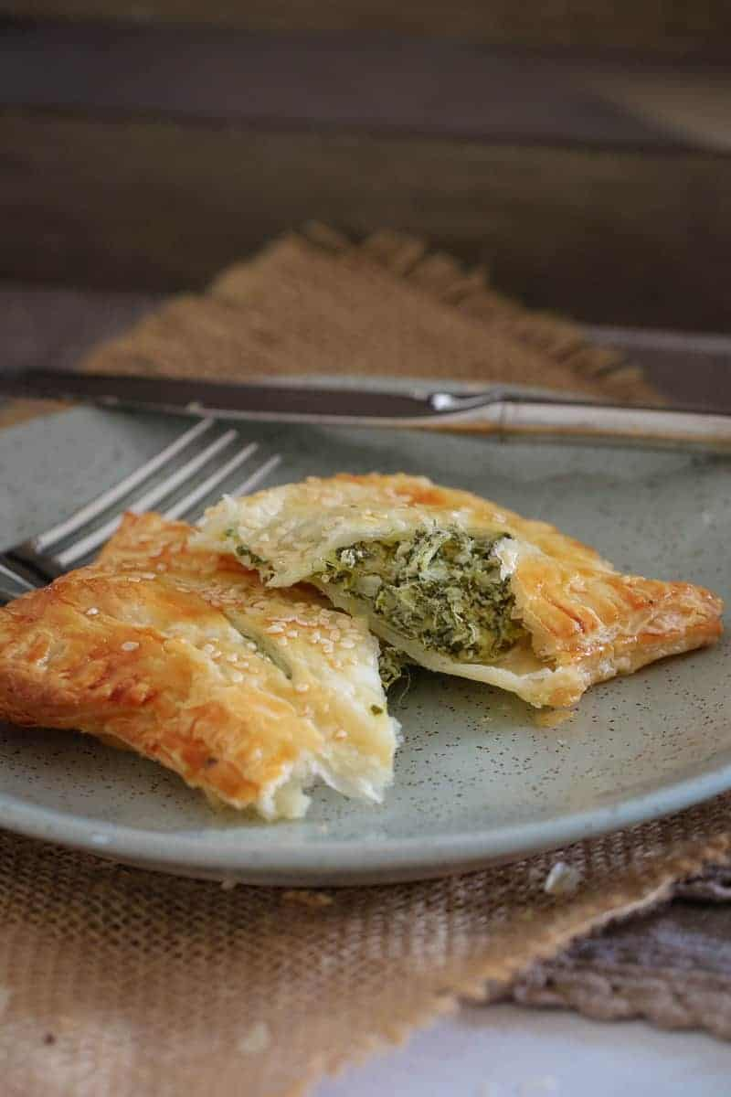 A golden puff pastry roll  on a plate, split to reveal a filling of spinach and ricotta
