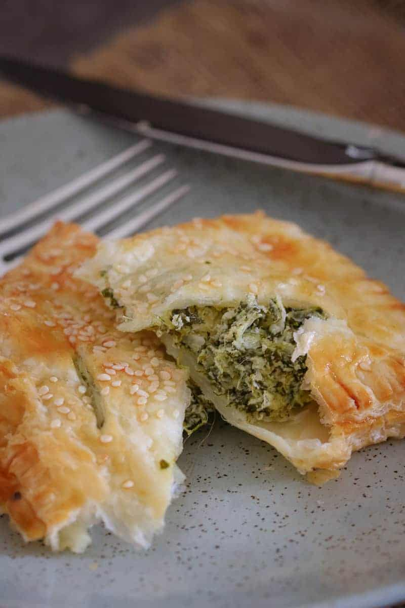 A close up of a golden pastry, split to reveal a filling of spinach and ricotta