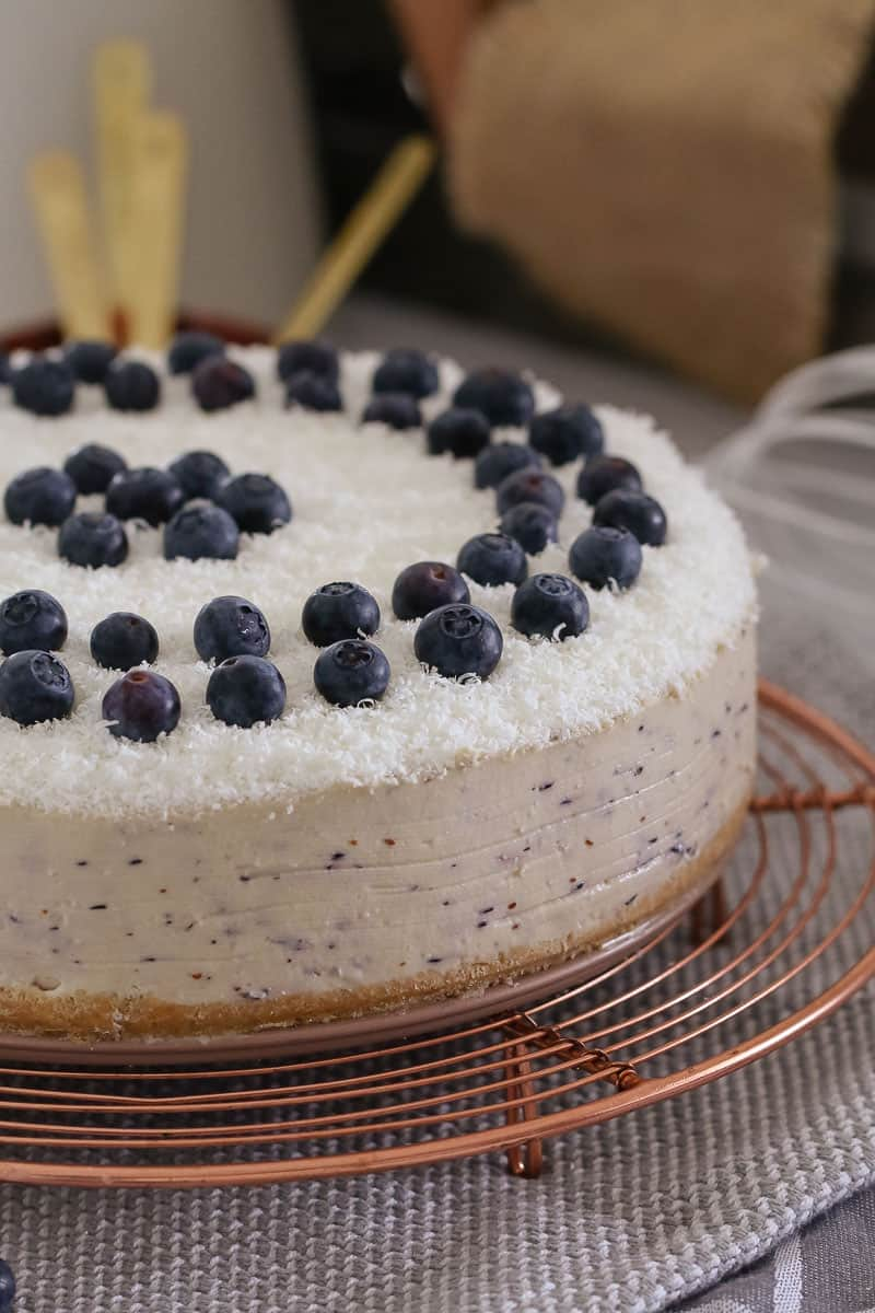 A delicious no-bake White Chocolate & Blueberry Cheesecake decorated with fresh blueberries and grated chocolate. This is the perfect summer dessert!
