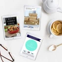 The three Thermomix recipe books of our Best Selling Bundle, on a white bench with a cup of lemon tea beside