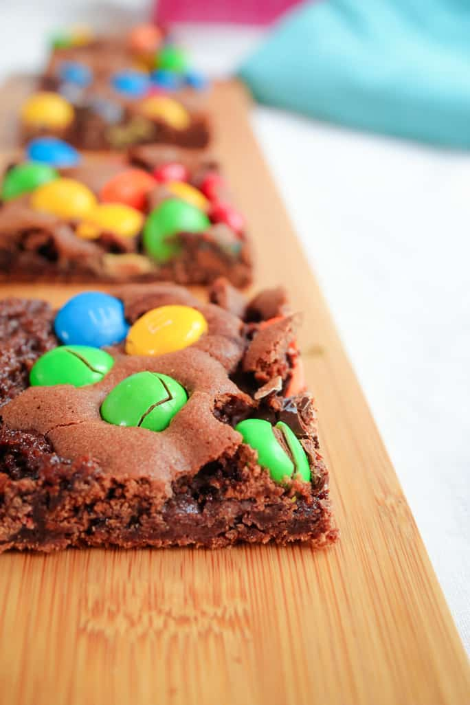A close up of a chocolate slice topped with coloured M&M's on a wooden board