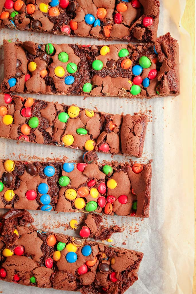 Looking down at cut pieces of a chocolate brownie slice topped with coloured M&M's