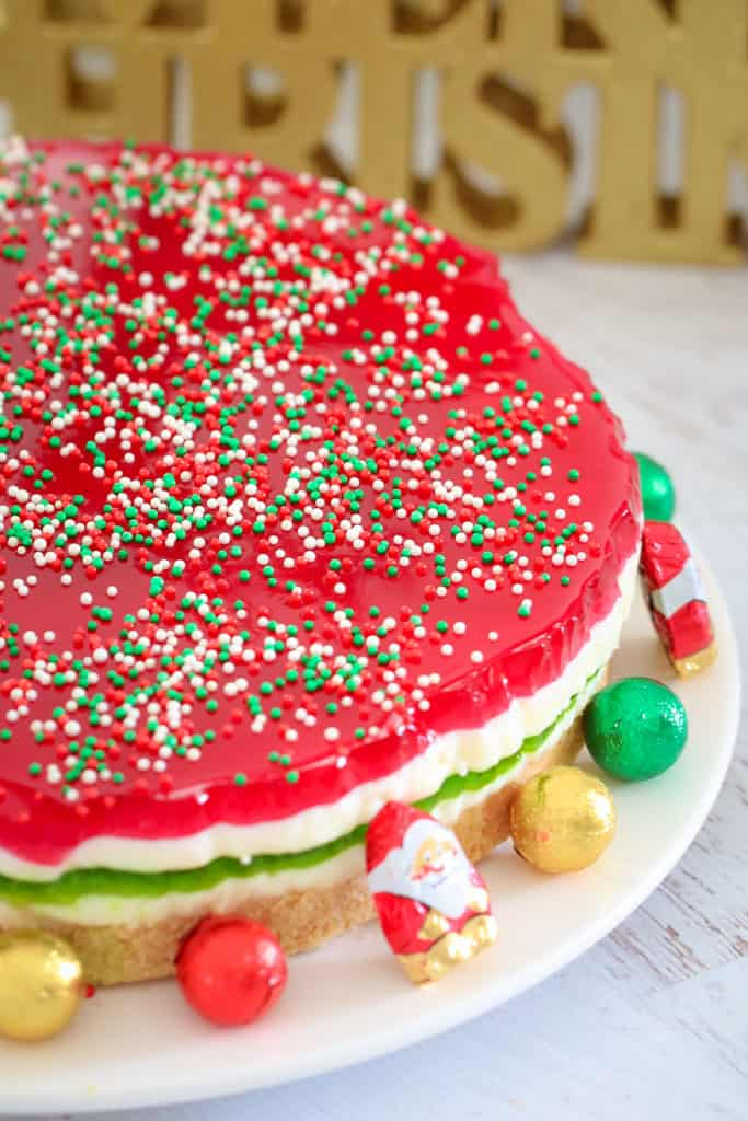 A close up of red, white and green layered Jelly Cake with sprinkles on top, and Christmas chocolates around the cake base