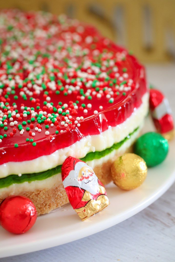 A close up a red, white and green Jelly Cake with sprinkles on top, and chocolate Santa\'s and balls on the plate
