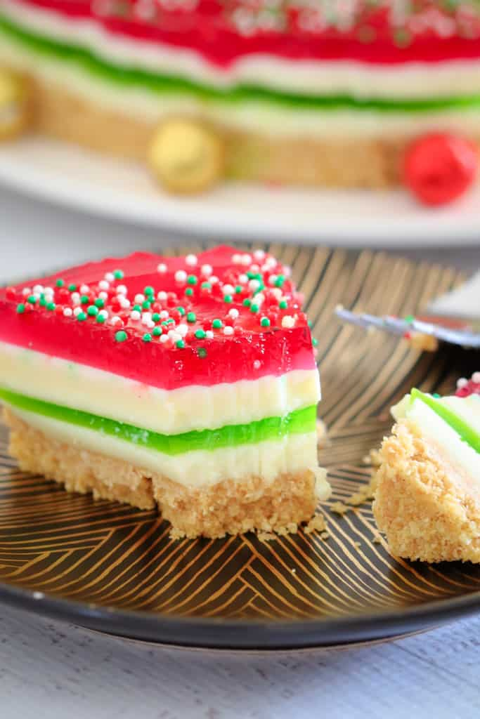 A serve of red, white and green layered Jelly Cake with sprinkles on top, on a black and gold plate